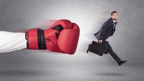 Ο επιχειρηματίας παίρνει ένα χτύπημα από ένα γιγαντιαίο χέρι ελεύθερη απεικόνιση δικαιώματος