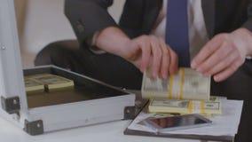 Ο επιχειρηματίας παίρνει έξω τα πακέτα δολαρίων από το χαρτοφύλακα, μέρη των χρημάτων απόθεμα βίντεο
