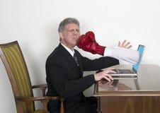 Ο επιχειρηματίας παίρνει την αιφνιδιαστική διάτρηση από το lap-top Στοκ φωτογραφία με δικαίωμα ελεύθερης χρήσης