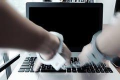 Ο επιχειρηματίας παραδίδει τις χειροπέδες στο ξύλινο γραφείο Στοκ εικόνα με δικαίωμα ελεύθερης χρήσης