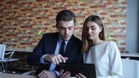 Ο επιχειρηματίας παρουσιάζει κάτι στη επιχειρηματία στον υπολογιστή ταμπλετών απόθεμα βίντεο