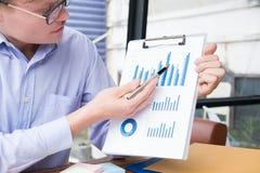 Ο επιχειρηματίας παρουσιάζει οικονομικό διάγραμμα γραφικών παραστάσεων στο γραφείο νεαρός άνδρας π Στοκ Εικόνα