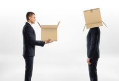 Ο επιχειρηματίας περνά το κιβώτιο στο άτομο με το χαρτόνι στο κεφάλι του Στοκ εικόνες με δικαίωμα ελεύθερης χρήσης