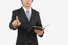 Ο επιχειρηματίας που δείχνει και που κρατά το βιβλίο σημειώσεων απομονώνει Στοκ φωτογραφία με δικαίωμα ελεύθερης χρήσης