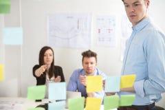 Ο επιχειρηματίας που εξετάζει την κόλλα σημειώνει δείχνοντας συναδέλφων Στοκ Φωτογραφία