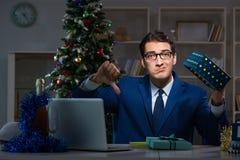 Ο επιχειρηματίας που εργάζεται αργά στη ημέρα των Χριστουγέννων στην αρχή στοκ φωτογραφία