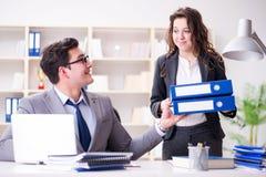 Ο επιχειρηματίας που ζητά τη γραφική εργασία από το βοηθητικό γραμματέα του στοκ εικόνες