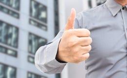 Ο επιχειρηματίας που παρουσιάζει αντίχειρες υπογράφει επάνω τη στάση στην αρχή Στοκ φωτογραφίες με δικαίωμα ελεύθερης χρήσης