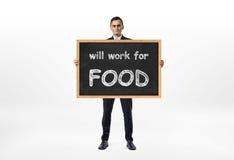 Ο επιχειρηματίας που στέκεται και που κρατά τον πίνακα με τις λέξεις ` θα εργαστεί για τα τρόφιμα ` γραπτά σε το Στοκ εικόνες με δικαίωμα ελεύθερης χρήσης