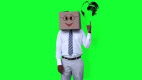 Ο επιχειρηματίας που φορά το κιβώτιο προσώπου smiley που δείχνει στη σφαίρα ενάντια απόθεμα βίντεο