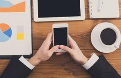 Ο επιχειρηματίας που χρησιμοποιεί το τηλέφωνο στον εργασιακό χώρο, τοπ άποψη, κλείνει επάνω Στοκ εικόνα με δικαίωμα ελεύθερης χρήσης
