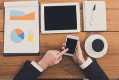 Ο επιχειρηματίας που χρησιμοποιεί το τηλέφωνο στον εργασιακό χώρο, τοπ άποψη, κλείνει επάνω Στοκ φωτογραφία με δικαίωμα ελεύθερης χρήσης