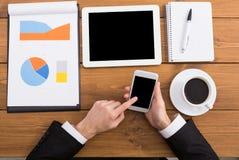 Ο επιχειρηματίας που χρησιμοποιεί το τηλέφωνο στον εργασιακό χώρο, τοπ άποψη, κλείνει επάνω Στοκ φωτογραφίες με δικαίωμα ελεύθερης χρήσης