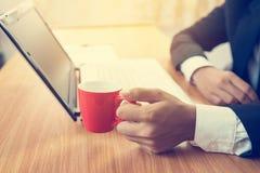 Ο επιχειρηματίας που χρησιμοποιεί το lap-top και πίνει τον καφέ Στοκ εικόνα με δικαίωμα ελεύθερης χρήσης