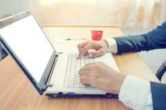 Ο επιχειρηματίας που χρησιμοποιεί το lap-top και πίνει τον καφέ Στοκ Εικόνες