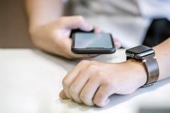 Ο επιχειρηματίας που χρησιμοποιεί το smartphone συνδέει με το smartwatch εργαζόμενος Στοκ εικόνες με δικαίωμα ελεύθερης χρήσης
