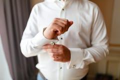 Ο επιχειρηματίας σε ένα άσπρο πουκάμισο ισιώνει τις μανσέτες, που στέκονται στο παράθυρο στο φυσικό φως Το άτομο κουμπώνει το μαν στοκ εικόνα με δικαίωμα ελεύθερης χρήσης