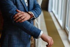 Ο επιχειρηματίας σε ένα γκρίζο σακάκι ρυθμίζει τα μανίκια Τελειοποιήστε στην τελευταία λεπτομέρεια Σύγχρονος επιχειρηματίας Μόδα  στοκ φωτογραφίες με δικαίωμα ελεύθερης χρήσης