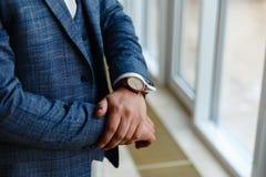 Ο επιχειρηματίας σε ένα γκρίζο σακάκι ρυθμίζει τα μανίκια Τελειοποιήστε στην τελευταία λεπτομέρεια Σύγχρονος επιχειρηματίας Μόδα  στοκ φωτογραφία με δικαίωμα ελεύθερης χρήσης