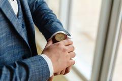 Ο επιχειρηματίας σε ένα γκρίζο σακάκι ρυθμίζει τα μανίκια Τελειοποιήστε στην τελευταία λεπτομέρεια Σύγχρονος επιχειρηματίας Μόδα  στοκ εικόνες