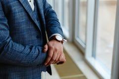Ο επιχειρηματίας σε ένα γκρίζο σακάκι ρυθμίζει τα μανίκια Τελειοποιήστε στην τελευταία λεπτομέρεια Σύγχρονος επιχειρηματίας Μόδα  στοκ εικόνα με δικαίωμα ελεύθερης χρήσης