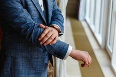 Ο επιχειρηματίας σε ένα γκρίζο σακάκι ρυθμίζει τα μανίκια Τελειοποιήστε στην τελευταία λεπτομέρεια Σύγχρονος επιχειρηματίας Μόδα  στοκ φωτογραφία