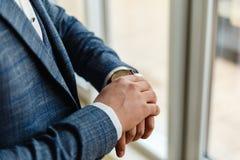 Ο επιχειρηματίας σε ένα γκρίζο σακάκι ρυθμίζει τα μανίκια Τελειοποιήστε στην τελευταία λεπτομέρεια Σύγχρονος επιχειρηματίας Μόδα  στοκ εικόνα