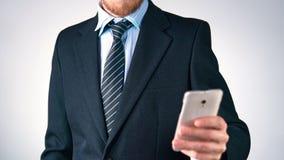 Ο επιχειρηματίας σε ένα κοστούμι με έναν δεσμό χρησιμοποιεί ένα κινητό τηλέφωνο κομψότητα, μοντέρνος τρόπος ζωής απόθεμα βίντεο