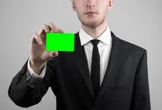 Ο επιχειρηματίας σε ένα μαύρο κοστούμι και έναν μαύρο δεσμό που κρατούν μια κάρτα, ένα χέρι που κρατά μια κάρτα, πράσινη κάρτα, κ Στοκ Εικόνες