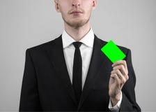 Ο επιχειρηματίας σε ένα μαύρο κοστούμι και έναν μαύρο δεσμό που κρατούν μια κάρτα, ένα χέρι που κρατά μια κάρτα, πράσινη κάρτα, κ Στοκ Εικόνα