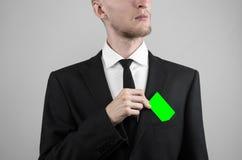 Ο επιχειρηματίας σε ένα μαύρο κοστούμι και έναν μαύρο δεσμό που κρατούν μια κάρτα, ένα χέρι που κρατά μια κάρτα, πράσινη κάρτα, κ Στοκ εικόνα με δικαίωμα ελεύθερης χρήσης