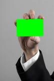 Ο επιχειρηματίας σε ένα μαύρο κοστούμι και έναν μαύρο δεσμό που κρατούν μια κάρτα, ένα χέρι που κρατά μια κάρτα, πράσινη κάρτα, κ Στοκ φωτογραφία με δικαίωμα ελεύθερης χρήσης
