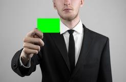 Ο επιχειρηματίας σε ένα μαύρο κοστούμι και έναν μαύρο δεσμό που κρατούν μια κάρτα, ένα χέρι που κρατά μια κάρτα, πράσινη κάρτα, κ Στοκ Φωτογραφίες