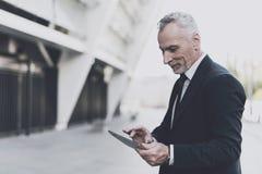Ο επιχειρηματίας σε ένα μαύρο κοστούμι ψάχνει σε μια ταμπλέτα Στοκ εικόνα με δικαίωμα ελεύθερης χρήσης
