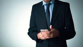 Ο επιχειρηματίας σε ένα μοντέρνο κοστούμι χρησιμοποιεί ένα τηλέφωνο κοινωνικότητα, κομψότητα φιλμ μικρού μήκους