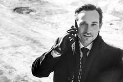 Ο επιχειρηματίας σε ένα σκοτεινό παλτό και τα γάντια, που μιλούν στο τηλέφωνο, ημέρα, κλείνει επάνω, υπαίθριος Στοκ φωτογραφίες με δικαίωμα ελεύθερης χρήσης