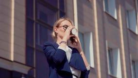 Ο επιχειρηματίας στέκεται κοντά στο κτίριο γραφείων, μιλά στο τηλέφωνο και κρατά ένα ποτήρι του καφέ Σε την δεξιά φιλμ μικρού μήκους
