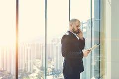Ο επιχειρηματίας στέκεται κοντά στο παράθυρο με το διάστημα αντιγράφων Στοκ Φωτογραφία