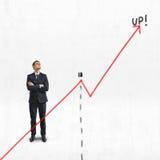 Ο επιχειρηματίας στέκεται με τα διπλωμένα όπλα ανοδικός πίσω από το μεγάλο διάγραμμα αύξησης, που απομονώνεται στο άσπρο υπόβαθρο Στοκ Εικόνα