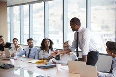 Ο επιχειρηματίας στέκεται να απευθυνθεί στη συνεδρίαση γύρω από τον πίνακα πινάκων στοκ εικόνα