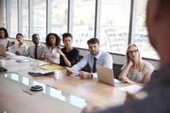 Ο επιχειρηματίας στέκεται να απευθυνθεί στη συνεδρίαση γύρω από τον πίνακα πινάκων στοκ φωτογραφίες με δικαίωμα ελεύθερης χρήσης