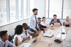 Ο επιχειρηματίας στέκεται να απευθυνθεί στη συνεδρίαση γύρω από τον πίνακα πινάκων στοκ φωτογραφία