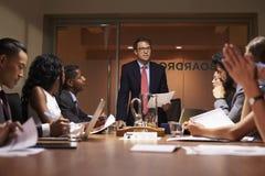 Ο επιχειρηματίας στέκεται στην ομάδα στη συνεδρίαση, χαμηλή γωνία στοκ εικόνα