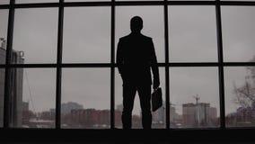 Ο επιχειρηματίας στέκεται στο παράθυρο στο γραφείο και εξετάζει την πόλη 4K φιλμ μικρού μήκους