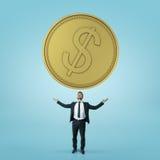 Ο επιχειρηματίας στέκεται τα χέρια του προς το μεγάλο χρυσό νόμισμα που απομονώνεται στο μπλε υπόβαθρο Στοκ φωτογραφία με δικαίωμα ελεύθερης χρήσης