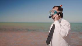 Ο επιχειρηματίας στην παραλία που μιλά στο τηλέφωνο σε μια κολυμπώντας με αναπνευτήρα μάσκα και κολυμπά με αναπνευτήρα απόθεμα βίντεο
