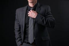 Ο επιχειρηματίας στη μαύρη καθιερώνουσα τη μόδα διόρθωση κοστουμιών δένει και κρατά ότι παραδώστε την τσέπη Στοκ εικόνες με δικαίωμα ελεύθερης χρήσης