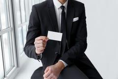 Ο επιχειρηματίας στη μαύρη παρουσίαση κοστουμιών είναι κάρτα Στοκ φωτογραφία με δικαίωμα ελεύθερης χρήσης