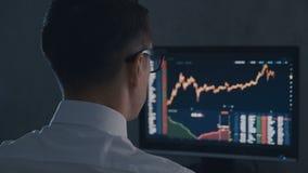 Ο επιχειρηματίας στο άσπρα πουκάμισο και τα γυαλιά αναλύει την αγορά πωλήσεων Η πίσω άποψη του χρηματιστή λειτουργεί με τη χρηματ φιλμ μικρού μήκους