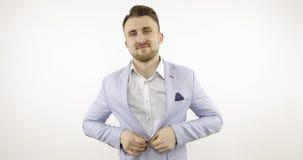 Ο επιχειρηματίας στο άσπρο πουκάμισο βάζει σε μια μπλε ζακέτα φιλμ μικρού μήκους